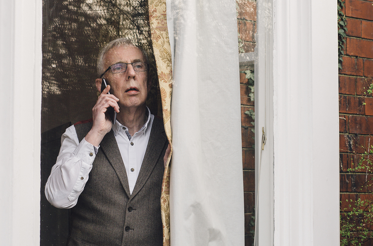 Man talking on the telephone while looking out of the window