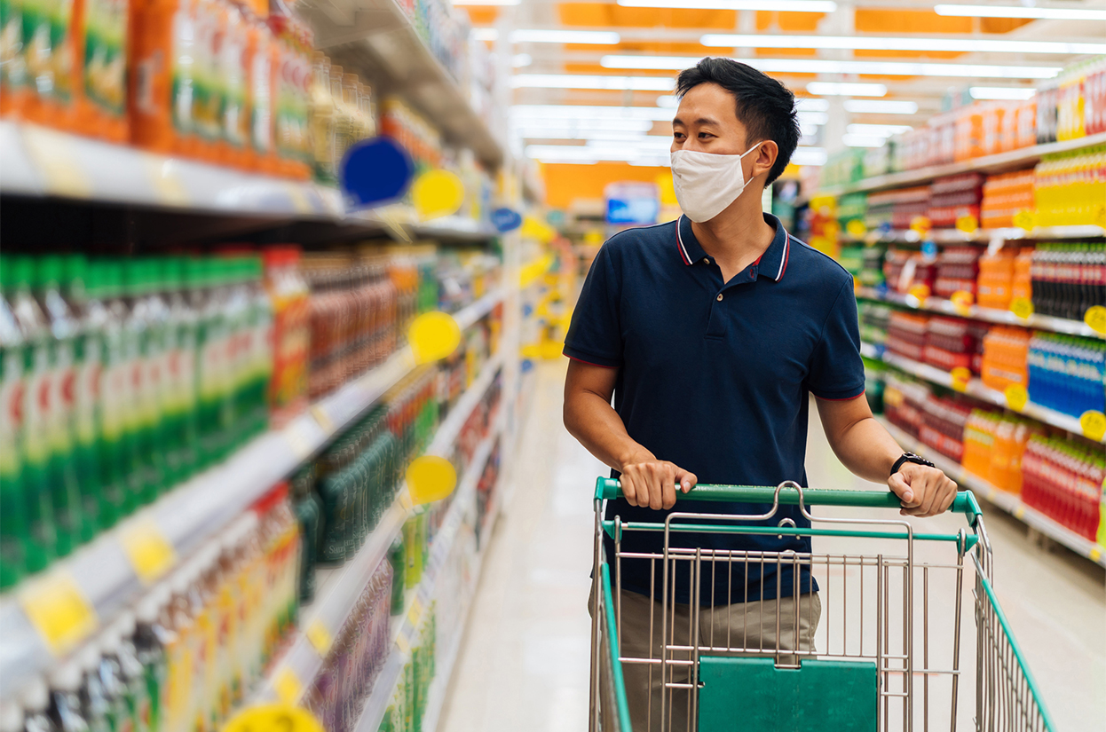 A young man shopping in a supermarket wearing a facemask
