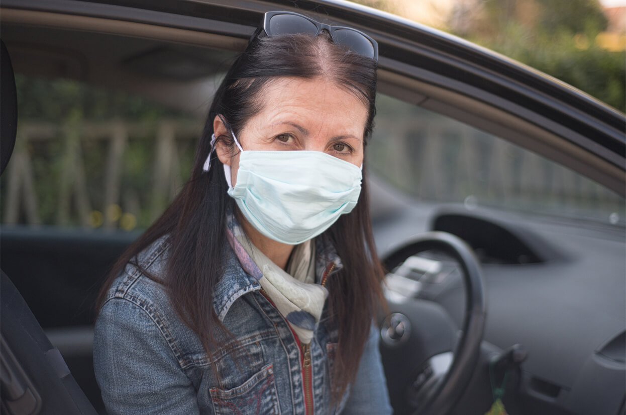 Volunteer in a car with a face mask