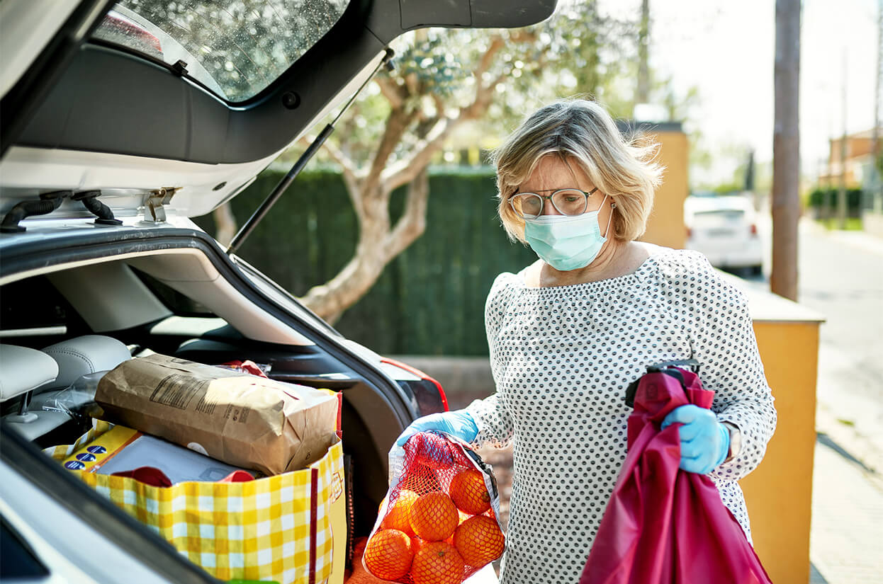 Woman unloading shopping from her car while wearing a face covering