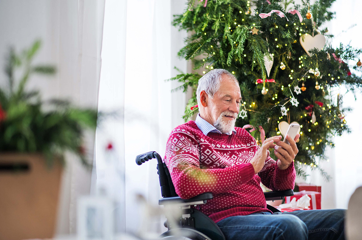 An older man sitting in a wheelchair in front of a decorated Christmas Tree while looking at a mobile phone