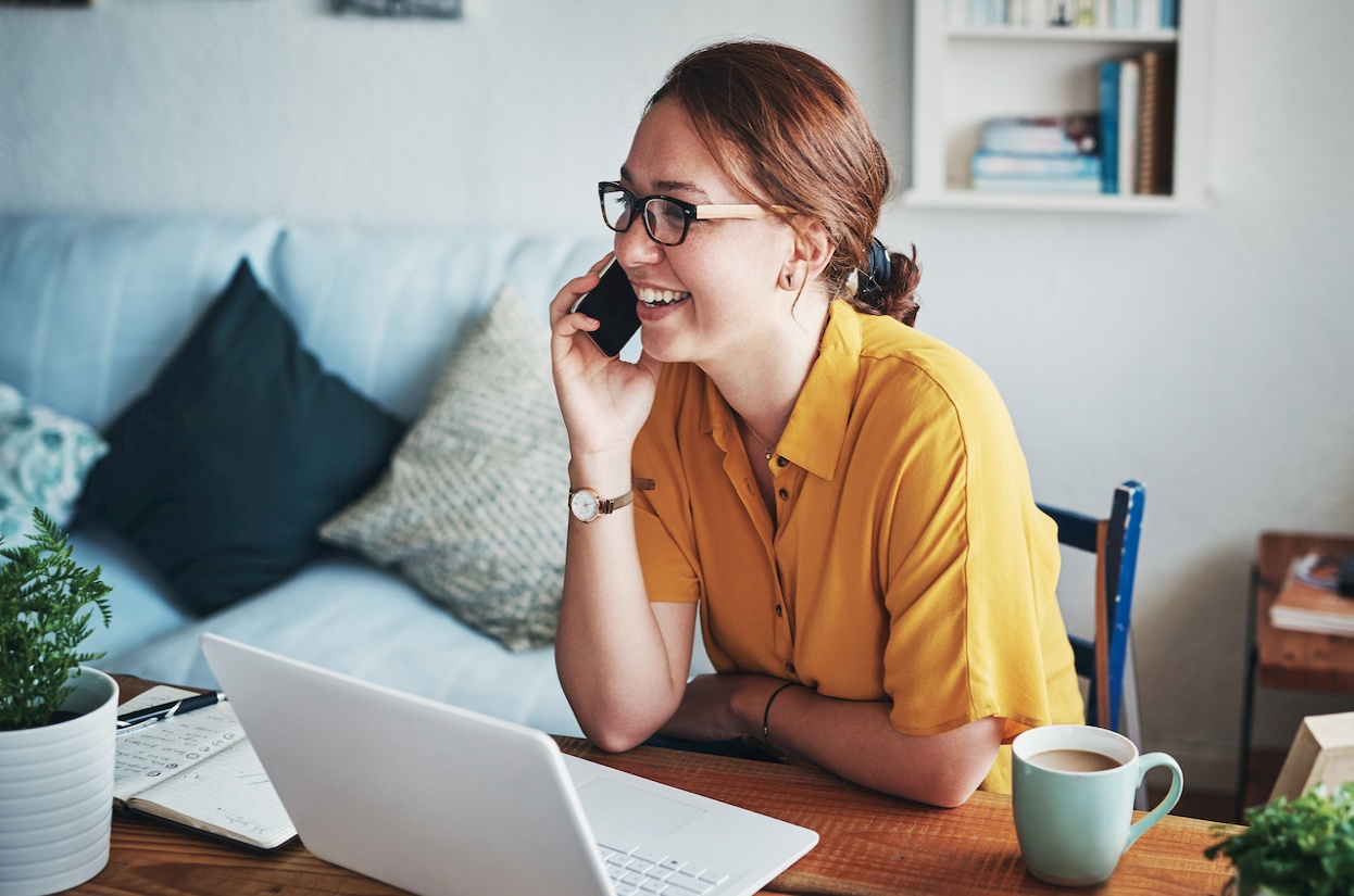 A younger woman working from home talking on a mobile phone