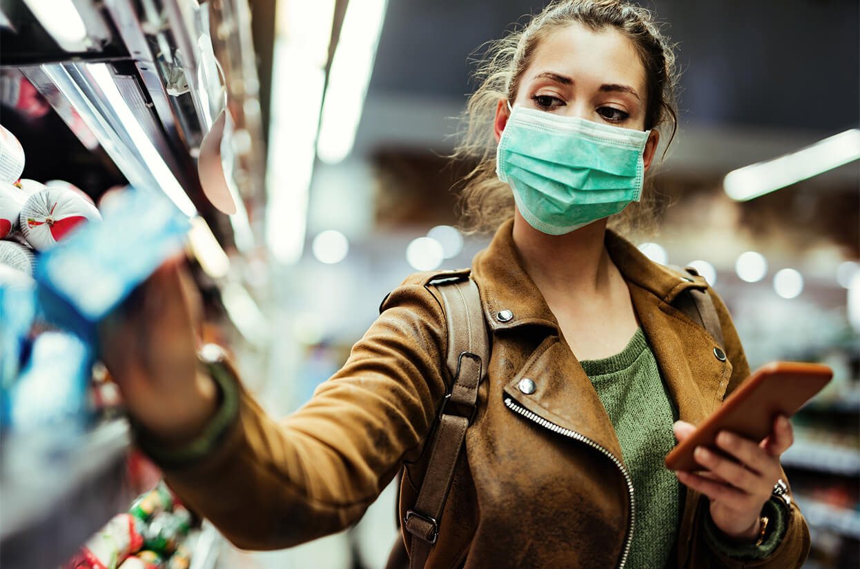 A younger woman doing shopping with a face mask on