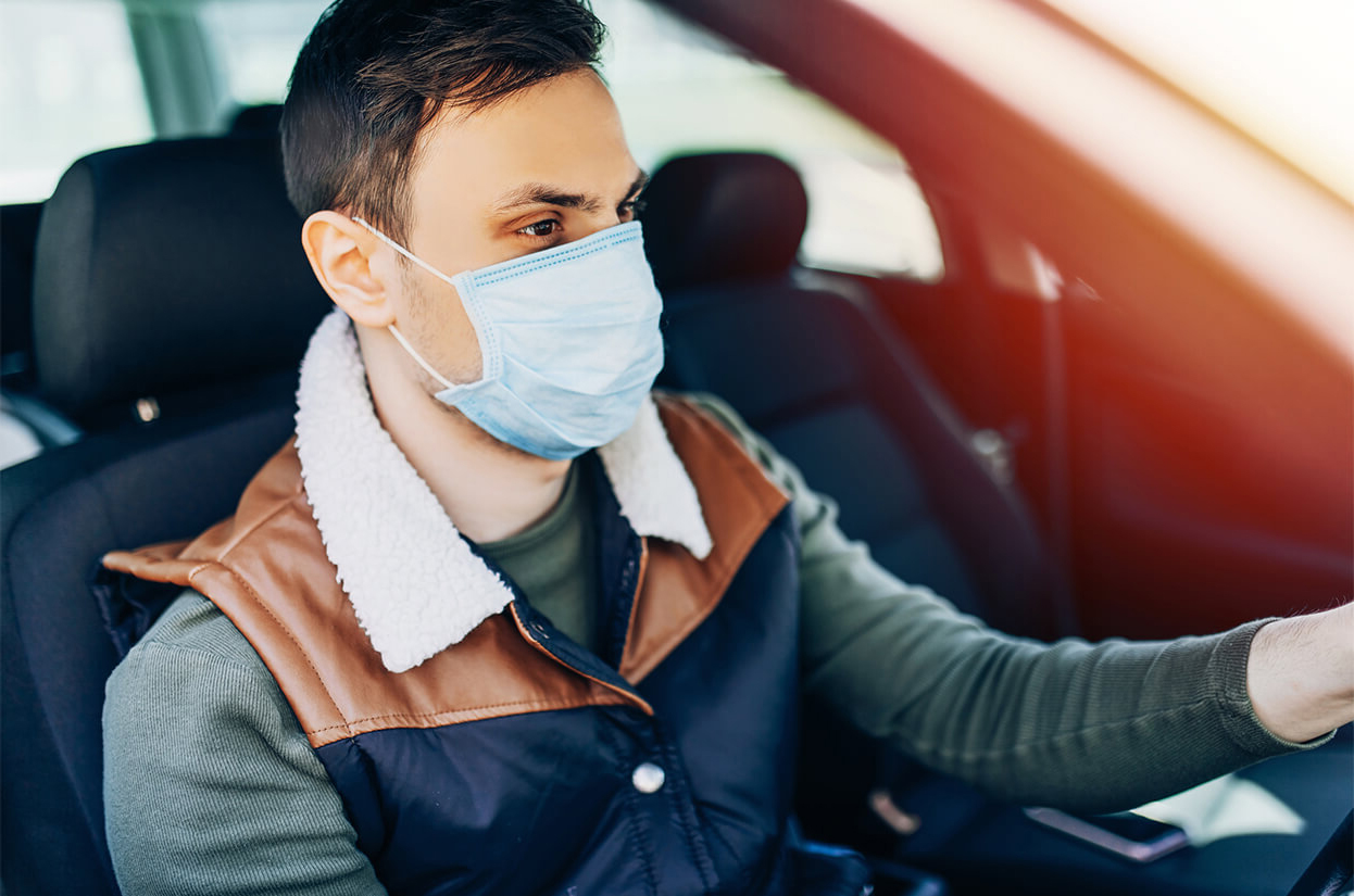 Young man volunteer driving while wearing a face mask