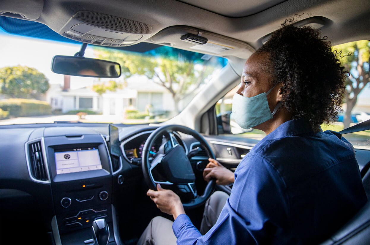 A young woman driving a car with a face mask on