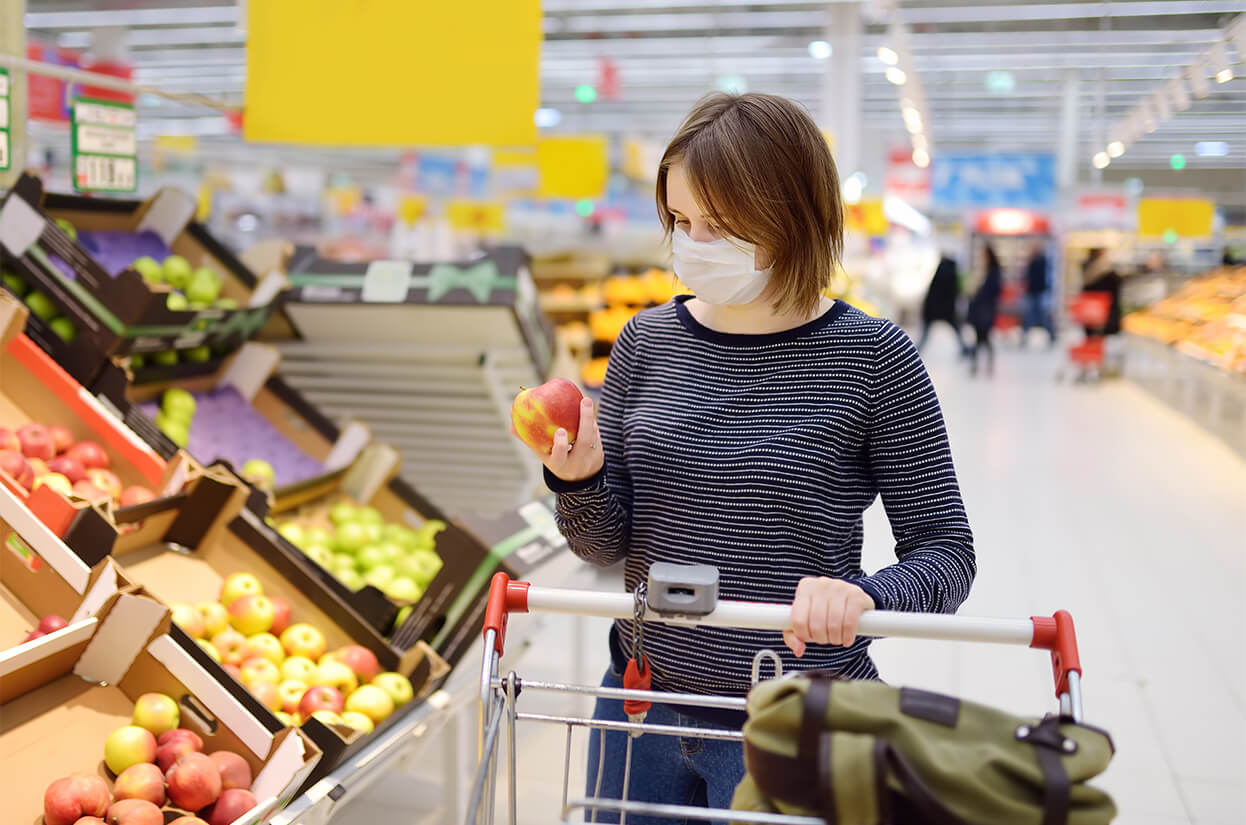 Younger woman shopping in a supermarket wearing a face covering