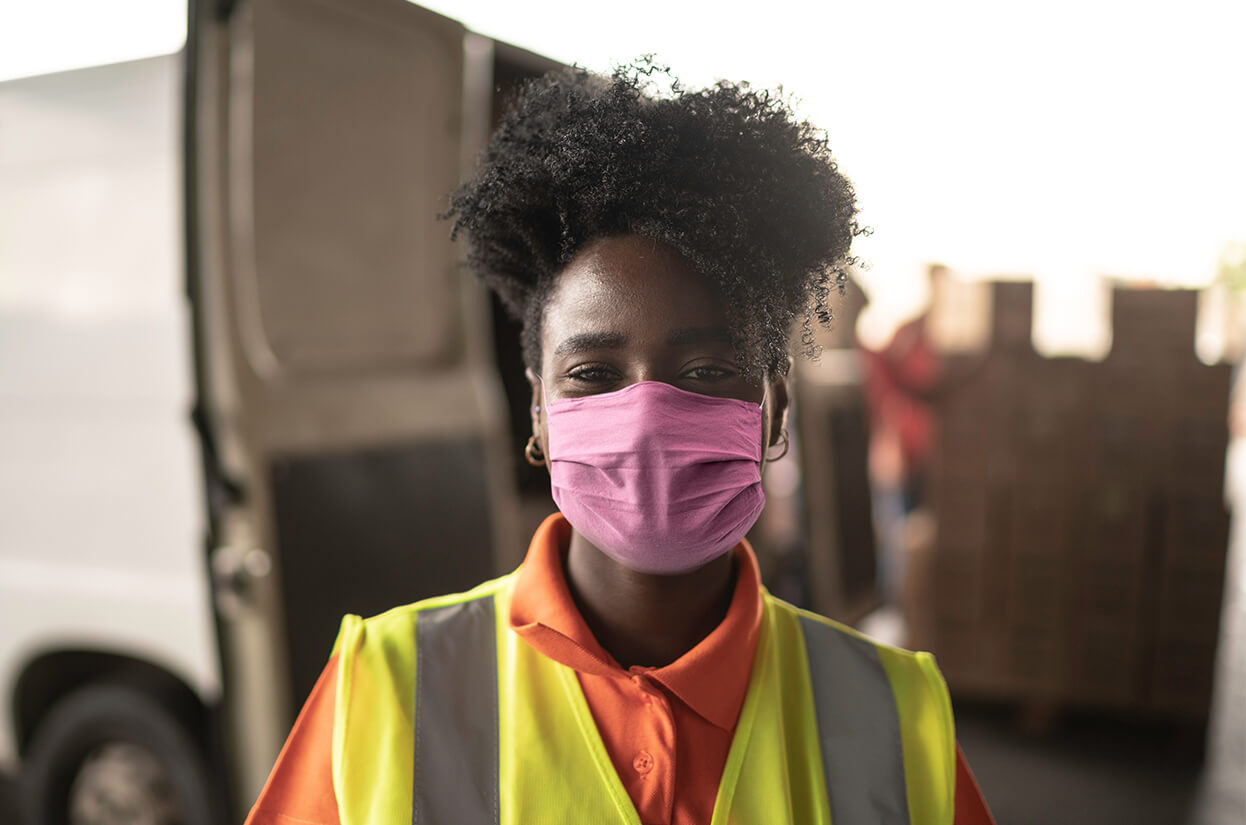 A young woman in a face mask wearing hi-viz