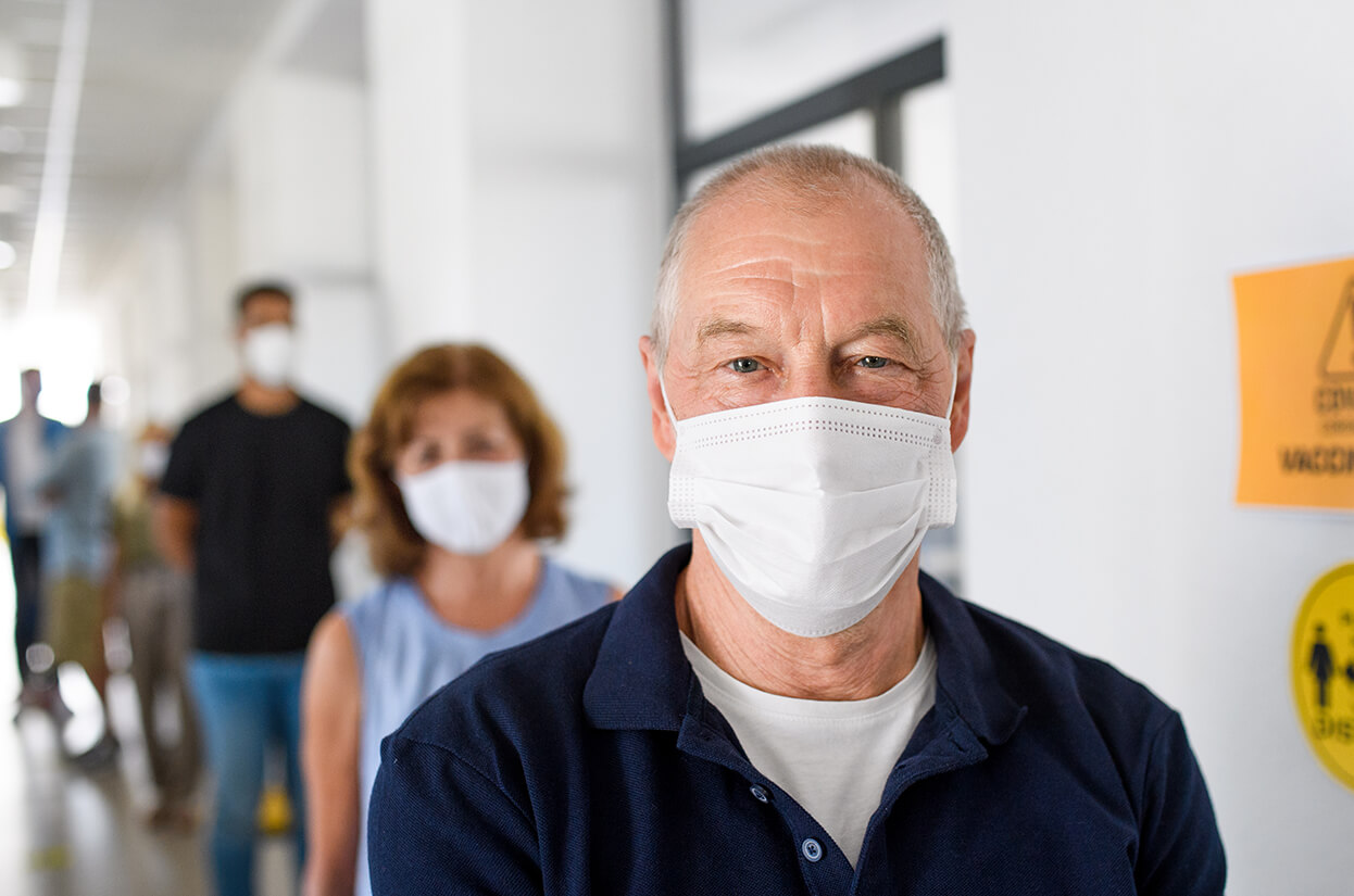 An older man wearing a mask in a queue for a flu vaccination