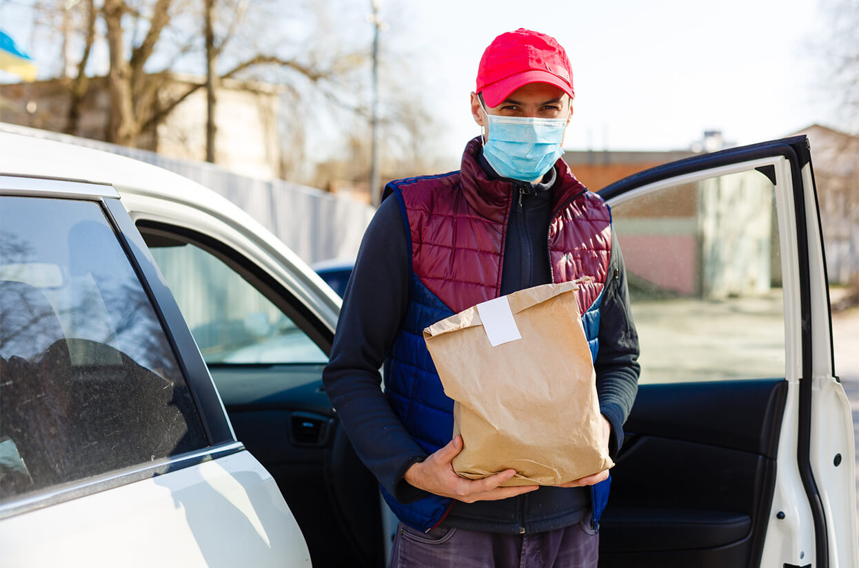 Young man getting out of a car with a face mask on carrying a package