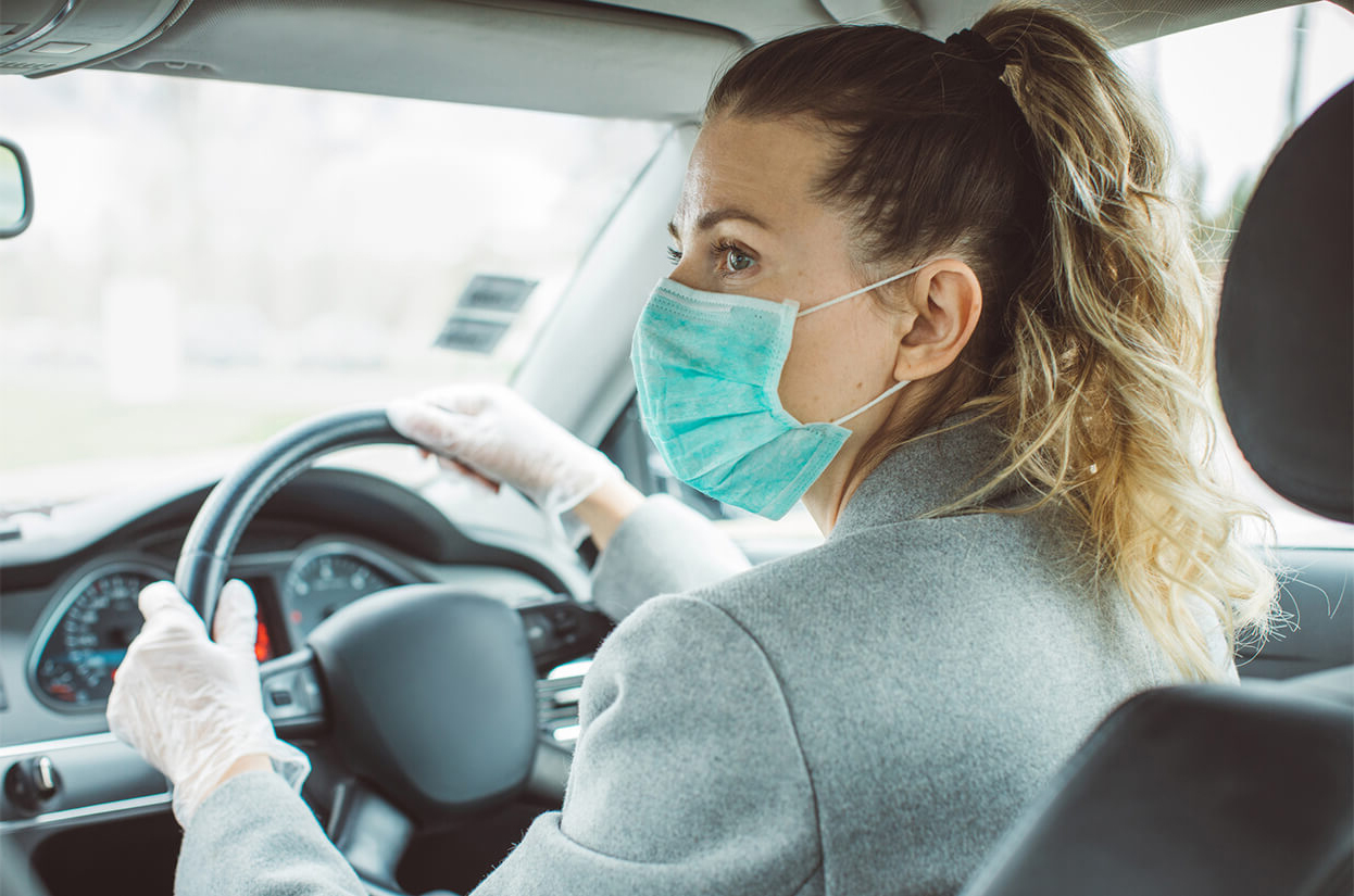 Young woman volunteer driving while wearing a face mask