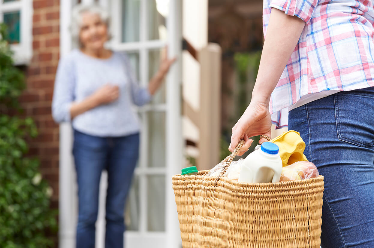 A volunteer delivering groceries to a vulnerable person